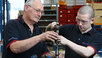 two fitters assemble a screw jack